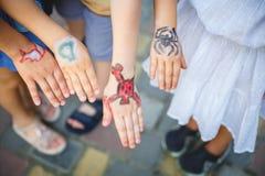 Gemaltes children& x27; s-Hände in den verschiedenen Farben mit smilies Lizenzfreie Stockfotografie