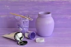 Gemaltes Glasgefäß, Bürste, Flieder und weiße Acrylfarbe Stockfotos