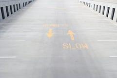 Gemaltes langsames Zeichen mit Pfeilen auf konkreter Rampe Stockfotos