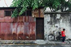 Gemaltes Mädchen und Junge, die wirkliches Fahrrad auf die alte Betonmauer von der Straße von George Town fährt Penang, Malaysia Lizenzfreie Stockbilder