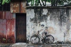 Gemaltes Mädchen und Junge, die wirkliches Fahrrad auf die alte Betonmauer von der Straße von George Town fährt Penang, Malaysia Stockfoto