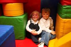 Gemaltes Mädchen und Junge sitzen im Kindergarten lizenzfreie stockbilder
