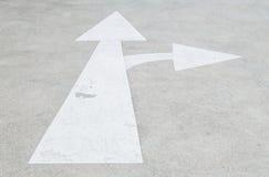 Gemaltes Pfeilzeichen der Nahaufnahme unterzeichnen Weiß auf Zementstraßen-Bodenhintergrund, gehen herein gerade und nach rechts  Stockfotos