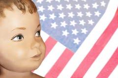 Gemaltes Retro- junges amerikanisches Jungengesicht der Puppe gegen verblaßten Hintergrund der amerikanischen Flagge stockfotos