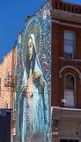 Gemaltes Wandgemälde auf Backsteinmauer in einer städtischen Stadt Stockbilder