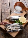 Gemarineerde ansjovissen met ruwe zout, citroen en peterselie Stock Foto's