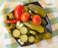 Gemarineerde komkommers, tomaten en courgette op een plaat Stock Foto's