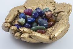 Gemas y cristales clasificados en manos de oro imagen de archivo libre de regalías