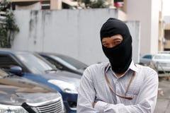 Gemaskeerde inbreker die balaclava dragen klaar aan inbraak tegen autoachtergrond Het concept van de verzekeringsmisdaad royalty-vrije stock afbeeldingen