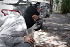 Gemaskeerde inbreker die balaclava dragen klaar aan inbraak tegen autoachtergrond Het concept van de verzekeringsmisdaad stock foto