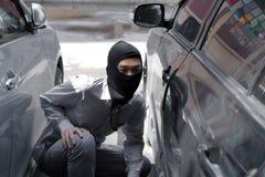Gemaskeerde inbreker die balaclava dragen klaar aan inbraak tegen autoachtergrond Het concept van de verzekeringsmisdaad stock afbeeldingen