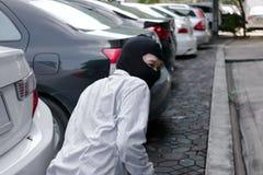 Gemaskeerde inbreker die balaclava dragen klaar aan inbraak tegen autoachtergrond Het concept van de verzekeringsmisdaad stock afbeelding