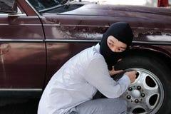 Gemaskeerde inbreker die balaclava dragen klaar aan inbraak tegen autoachtergrond Het concept van de verzekeringsmisdaad stock fotografie