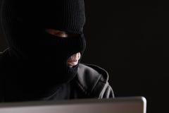 Gemaskeerde Misdadiger die Computer tot Gegevens toegang hebben Royalty-vrije Stock Afbeeldingen