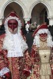 Gemaskeerde personen in prachtig rood en gouden kostuum op San Marco Stock Afbeeldingen