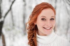 Gember glimlachend meisje in witte sweater in de winter bossneeuw december in park Portret Kerstmis leuke tijd Stock Foto's