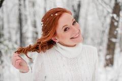 Gember mooi meisje in witte sweater in de winter bossneeuw december in park Portret Kerstmis leuke tijd Royalty-vrije Stock Afbeelding