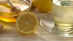 Gemberthee met citroen, munt en honing op houten achtergrond stock videobeelden