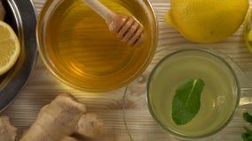 Gemberthee met citroen, munt en honing op houten achtergrond stock footage