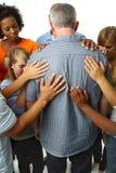 Gemeenschap van mensen die voor een oudere mens bidden royalty-vrije stock foto's