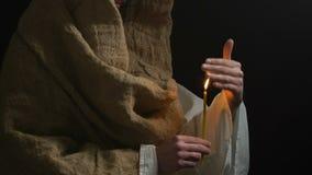 Gemeindemitglied in der Robe, die brennende Kerze, betenden Gott, bitten um Hilfe hält stock video