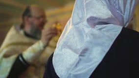 Gemeindemitglieder küssen das Kirchenkreuz stock video
