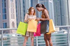 Gemeinsame Anschaffungen Zwei Freundinnen in den Kleidern, die Einkaufsba halten Stockfoto