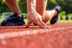 Gemeinsame Sorgfalt für Läufer Hand des Sportlers auf niedriger Position der Laufbahn Anfangs Läufer bereit, nah oben zu gehen en lizenzfreie stockfotos