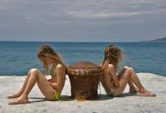 Gemella le sorelle sul falò in porto marittimo Fotografie Stock