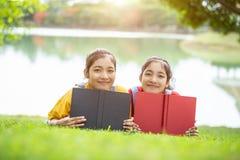 Gemelli abbastanza asiatici ragazza o studenti che legge un libro nel pubblico Fotografie Stock Libere da Diritti