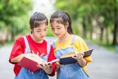 Gemelli abbastanza asiatici ragazza o studenti che legge un libro nel pubblico Immagini Stock Libere da Diritti