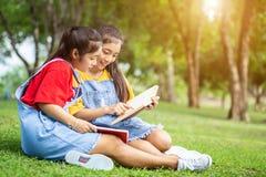Gemelli abbastanza asiatici ragazza o studenti che legge un libro nel pubblico Immagine Stock