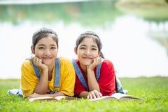 Gemelli abbastanza asiatici ragazza o studenti che legge un libro nel pubblico Fotografia Stock
