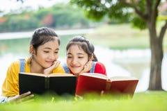 Gemelli abbastanza asiatici ragazza o studenti che legge un libro nel pubblico Fotografie Stock