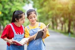 Gemelli abbastanza asiatici ragazza o studenti che legge un libro nel pubblico Immagini Stock