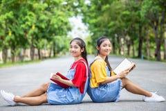 Gemelli abbastanza asiatici ragazza o studenti che legge un libro nel pubblico Fotografia Stock Libera da Diritti