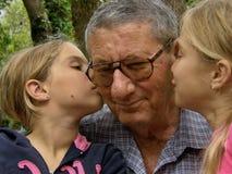 Gemelli, bacio delle sorelle al nonno Fotografia Stock Libera da Diritti