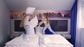 Gemelli che combattono con i cuscini sul letto video d archivio