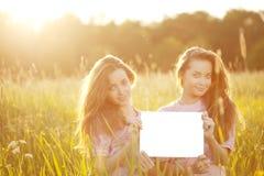 Gemelli che tengono manifesto in bianco bianco all'aperto Fotografia Stock