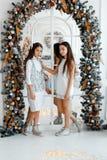 Gemelli delle ragazze davanti allo specchio del thearch ` S EVE del nuovo anno Natale Festa accogliente all'abete con le luci fotografia stock