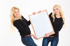 Gemelli sorridenti delle sorelle che tengono bordo in bianco Immagine Stock