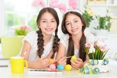 Gemelli svegli che indossano le orecchie di coniglio che decorano le uova di Pasqua fotografia stock libera da diritti