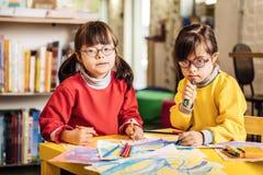 Gemelli svegli con la sensibilità di sindrome di Down in questione nelle immagini di coloritura immagini stock