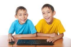 Gemelos con el ratón y el teclado del ordenador Foto de archivo libre de regalías