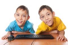 Gemelos con el ratón y el teclado del ordenador Fotografía de archivo