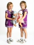 Gemelos de las hermanas con las muñecas Fotos de archivo libres de regalías
