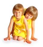 Gemelos de las hermanas en alineadas amarillas Fotografía de archivo