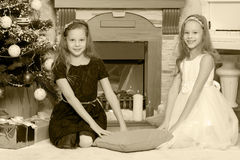 Gemelos de las muchachas con el árbol de navidad de los regalos e Fotografía de archivo