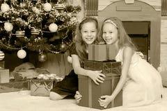 Gemelos de las muchachas con el árbol de navidad de los regalos e Imagenes de archivo