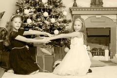 Gemelos de las muchachas con el árbol de navidad de los regalos e Imagen de archivo libre de regalías